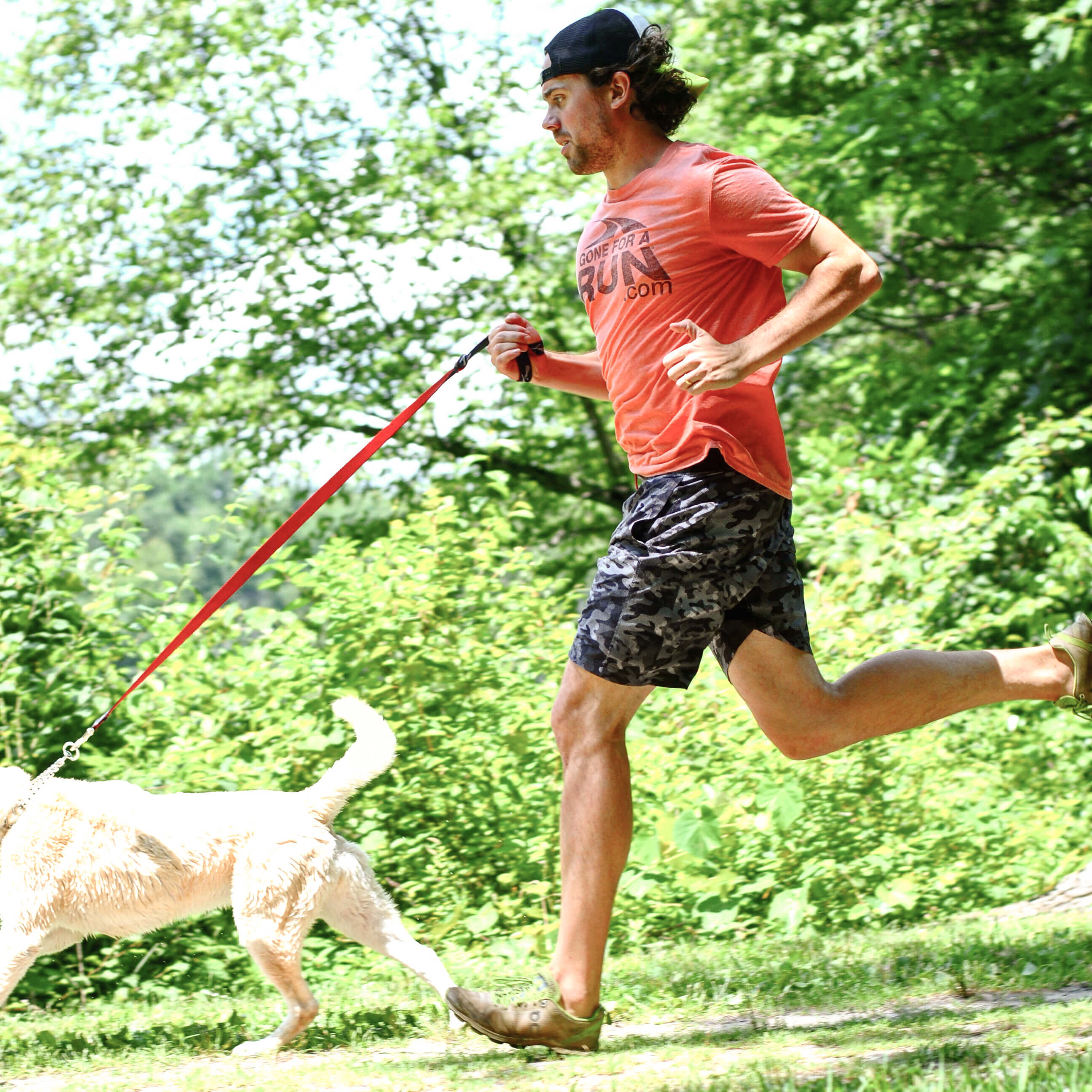 Guy running with his dog in the woods